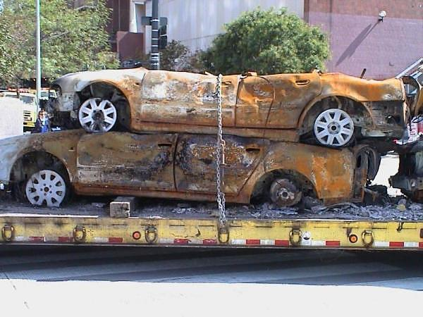 New cars with alloy rims being hauled away from ground zero. Notice the rust created by WTC nuclear blast